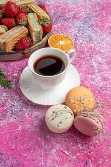 Leckere kekssandwiches mit erdbeeren und macarons und kaffeetasse