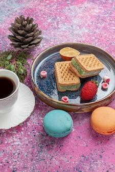 Leckere kekssandwiches mit macarons und kaffeetasse