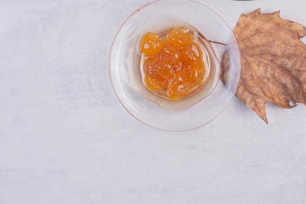 Leckere kirschmarmelade mit blatt auf weißem tisch.