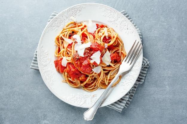 Leckere klassische italienische pasta mit tomatensauce und käse auf dem teller. ansicht von oben.