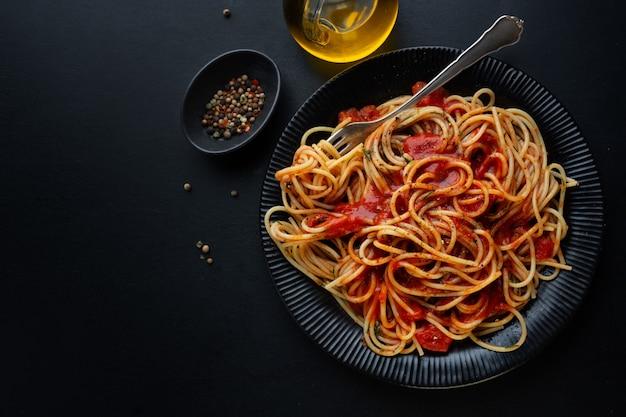 Leckere klassische italienische pasta mit tomatensauce und käse auf dem teller auf dunklem hintergrund. ansicht von oben.