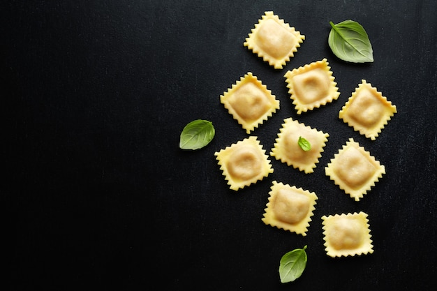 Leckere klassische italienische ravioli mit basilikum auf dunklem hintergrund. draufsicht.