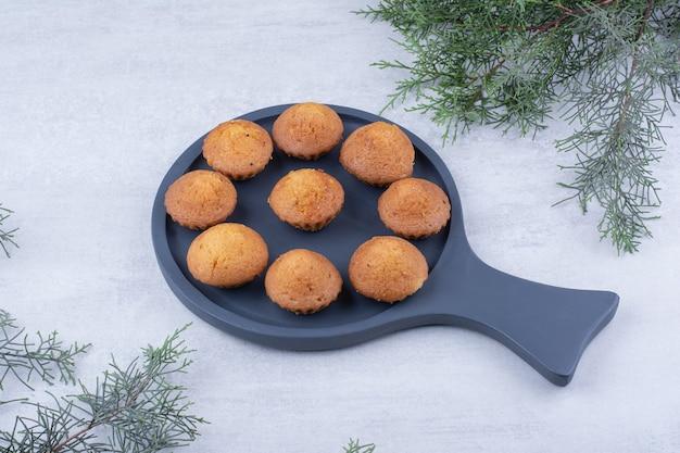 Leckere kleine kuchen auf teller mit tannenzweig.