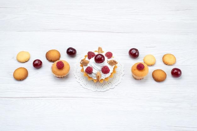Leckere kleine kuchen mit himbeeren zusammen mit keksen auf licht