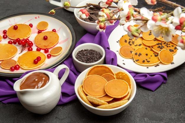 Leckere kleine pfannkuchen mit keksen auf schwarz
