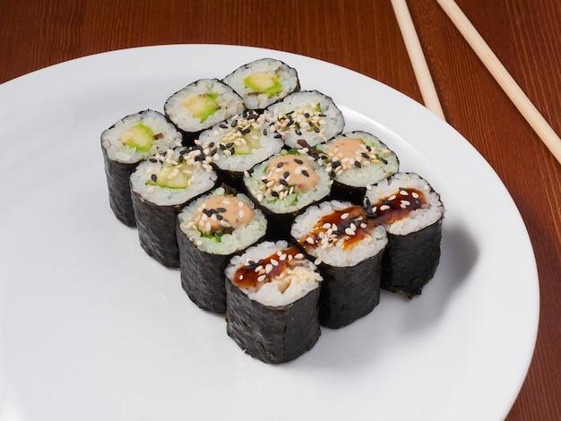 Leckere kleine sushi-rollen auf einem weißen teller