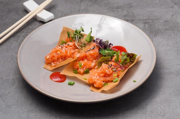 Leckere knusprige chips mit leicht gesalzenem lachs und scharfer sauce