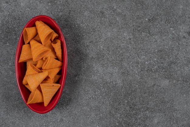 Leckere knusprige pommes in roter schüssel.