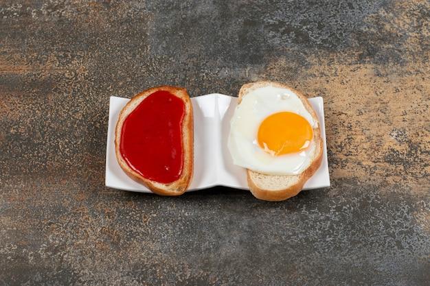 Leckere knusprige toasts mit spiegelei und marmelade.