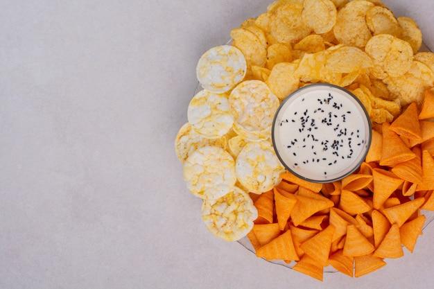 Leckere kreuzkartoffelchips mit joghurt auf weißem hintergrund. hochwertiges foto