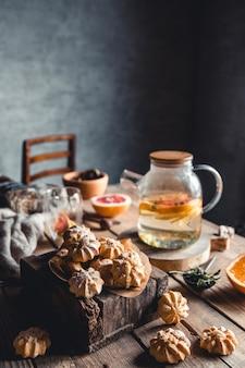 Leckere kuchen mit heißem tee mit scheiben frischer grapefruit auf holztafel. gesundes getränk, öko, vegan