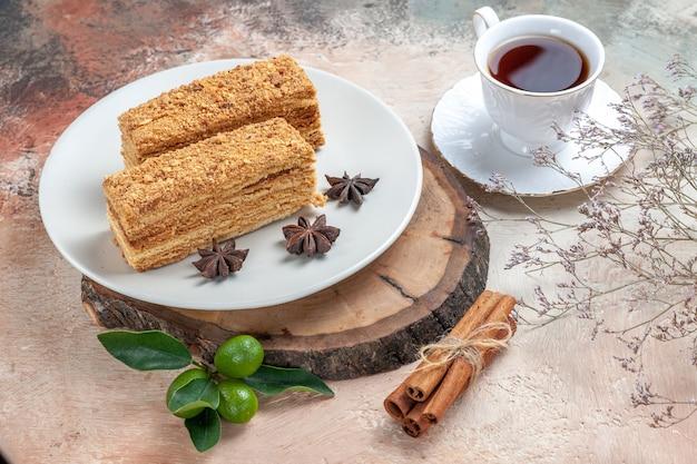 Leckere kuchenstücke mit einer tasse tee auf grau