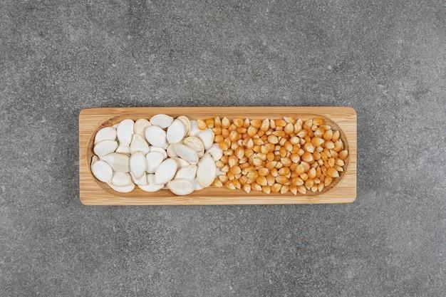 Leckere kürbiskerne und maiskörner auf holzteller.