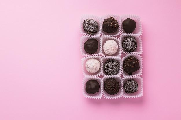 Leckere kugelförmige pralinen verpackt in kleinen papierkörben auf rosa hintergrund. dessert zum romantischen valentinstag. köstlich süß. minimaler stil. flache lage, draufsicht mit kopierlandschaft.