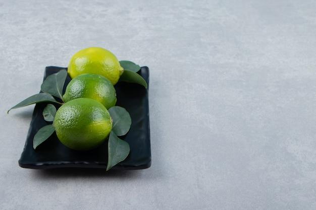 Leckere limettenfrüchte auf schwarzem teller