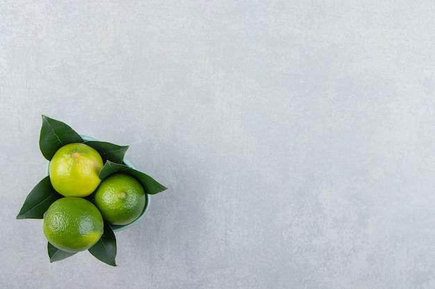 Leckere limettenfrüchte in blauer schale