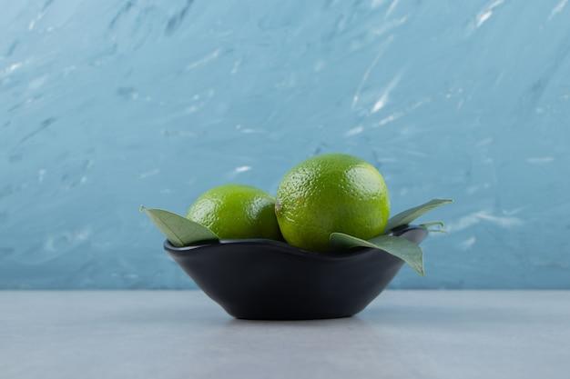 Leckere limettenfrüchte in schwarzer schale
