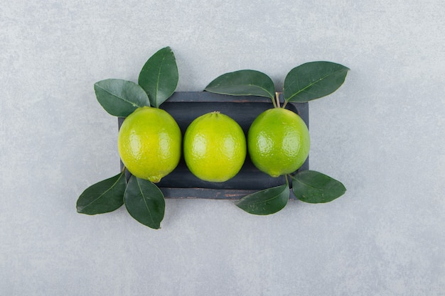 Leckere limettenfrüchte mit blättern auf schwarzem teller