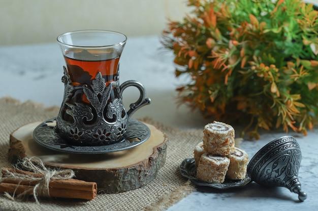 Leckere lokum-desserts und ein glas tee auf steinoberfläche.