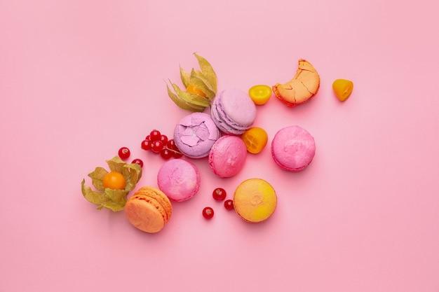 Leckere macarons mit früchten auf farbigem hintergrund