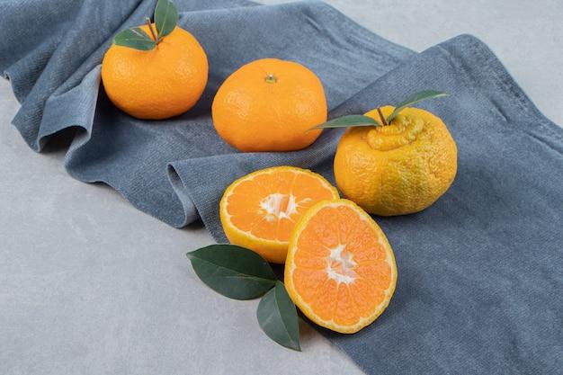 Leckere mandarinenfrüchte auf blauem tuch