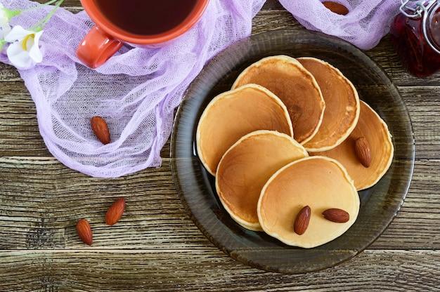 Leckere mandelpfannkuchen mit tee und marmelade auf einem holztisch. draufsicht.