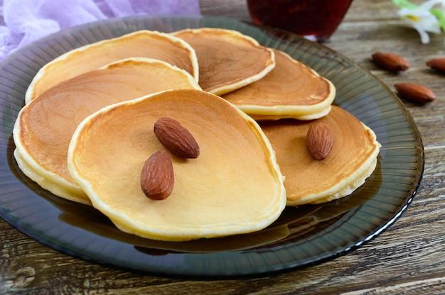 Leckere mandelpfannkuchen mit tee und marmelade auf einem holztisch. nahansicht