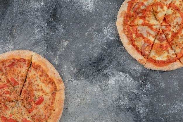 Leckere margherita und würzige hühnerpizza auf steinhintergrund.