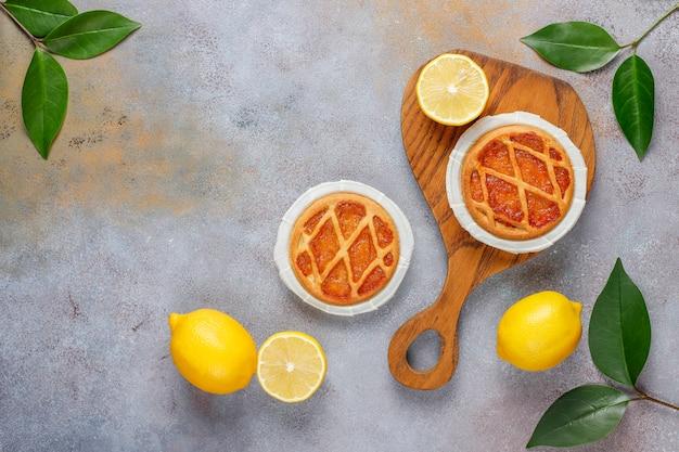 Leckere mini-zitronenkuchen mit frischen zitronen, draufsicht