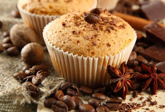 Leckere muffinkuchen mit schokolade, gewürzen und kaffeesamen, auf beigem hintergrund