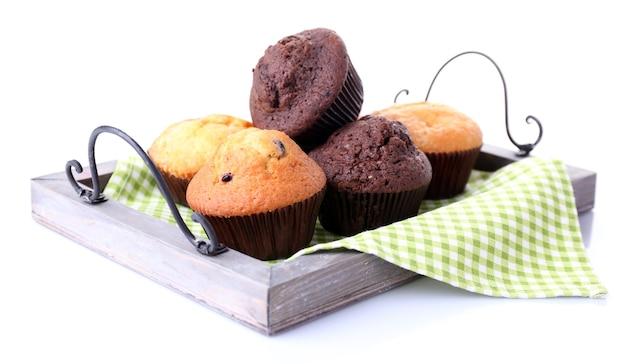 Leckere muffins auf holztablett lokalisiert auf weiß