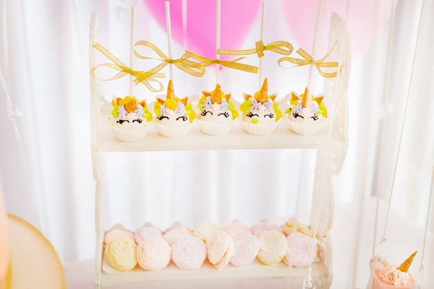 Leckere muffins in form von einhorn und marshmallows auf zweistufigen ständen
