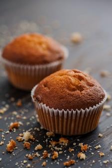Leckere muffins mit den krümeln auf der holzoberfläche