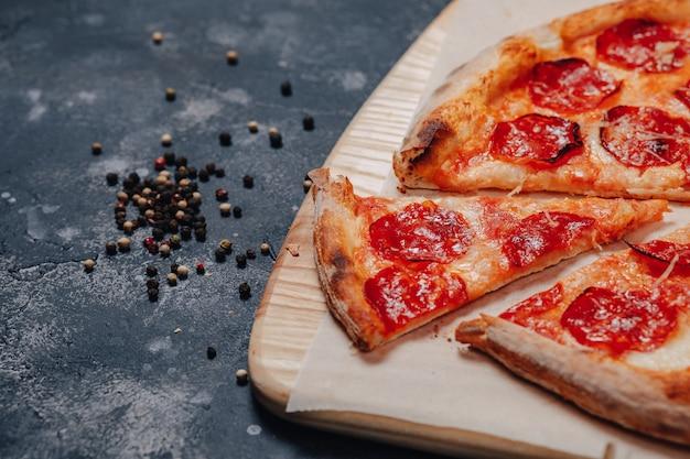 Leckere neapolitanische pizza auf einer tafel mit verschiedenen zutaten