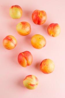 Leckere nektarinen auf einer rosa oberfläche. flach liegen.
