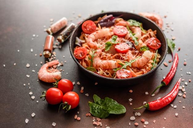 Leckere nudeln mit garnelen und tomaten auf einer pfanne