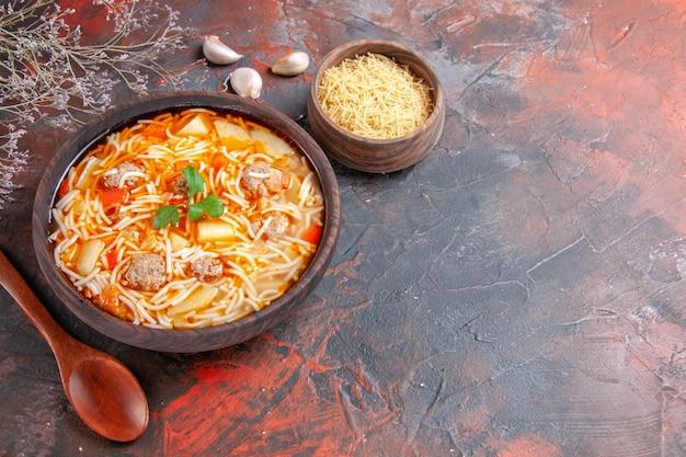 Leckere nudelsuppe mit hühnchen und ungekochten nudeln in einer kleinen braunen schüssel und löffel auf dunklem hintergrund