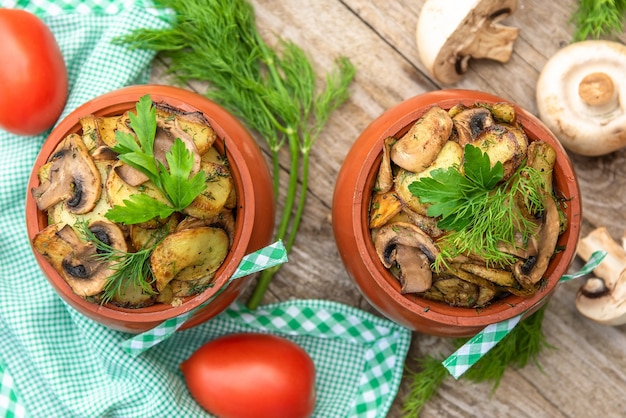 Leckere ofenkartoffeln mit pilzen und fleisch im ofen. auf einem holztisch. draufsicht.