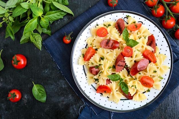 Leckere pasta farfalle mit gegrillten würstchen, frischen kirschtomaten und basilikum auf einem teller auf einem schwarzen tisch. draufsicht, flach liegen.