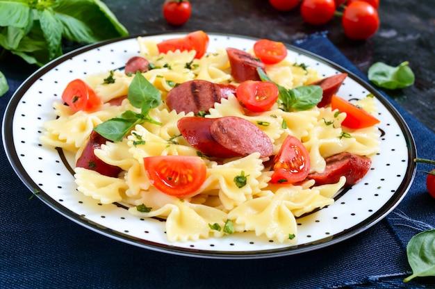 Leckere pasta farfalle mit gegrillten würstchen, frischen kirschtomaten und basilikum auf einem teller auf einem schwarzen tisch