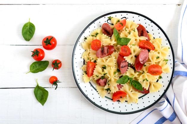 Leckere pasta farfalle mit gegrillten würstchen, frischen kirschtomaten und basilikum auf einem teller auf einem weißen holztisch. draufsicht, flach liegen.