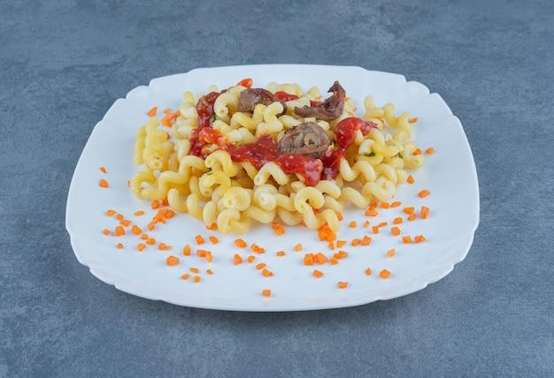 Leckere pasta mit fleischstücken auf weißem teller.
