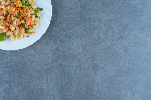 Leckere pasta mit gehacktem gemüse auf weißem teller.