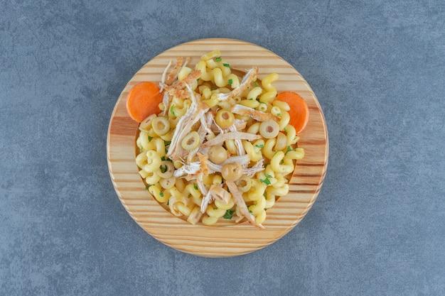 Leckere pasta mit gehacktem hühnchen auf holzplatte.