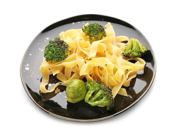 Leckere pasta mit gemüse auf weißem hintergrund