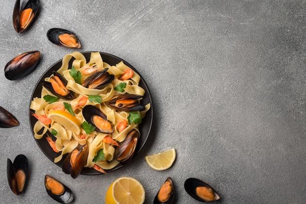 Leckere pasta mit muscheln, tintenfisch, petersilie und zitrone, ansicht von oben.