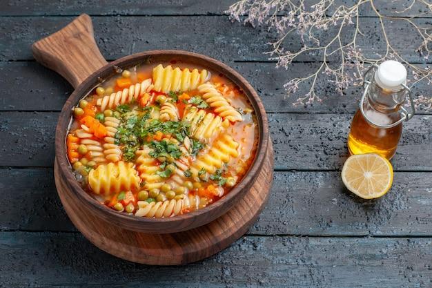 Leckere pastasuppe mit halber draufsicht aus spiralförmiger italienischer pasta mit grüns auf dunkelblauem schreibtisch suppenteller farbe italienische pasta-küche