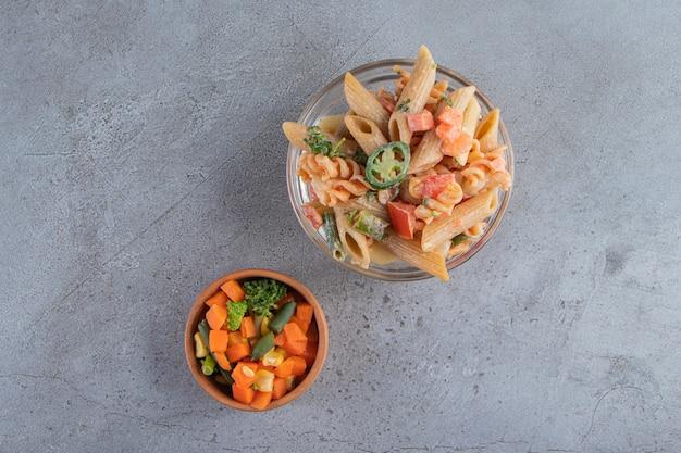 Leckere penne-nudeln und frischer salat auf steinhintergrund.