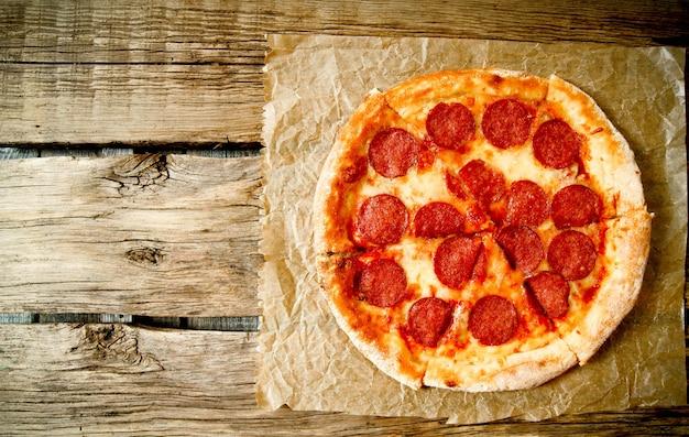 Leckere peperoni-pizza auf einem alten papier. auf einem hölzernen hintergrund.