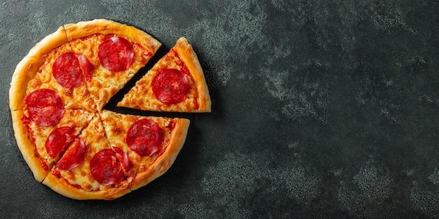 Leckere peperoni-pizza und kochende zutaten tomaten basilikum auf schwarz